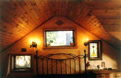 lighted room with vaulted ceiling and wood walls