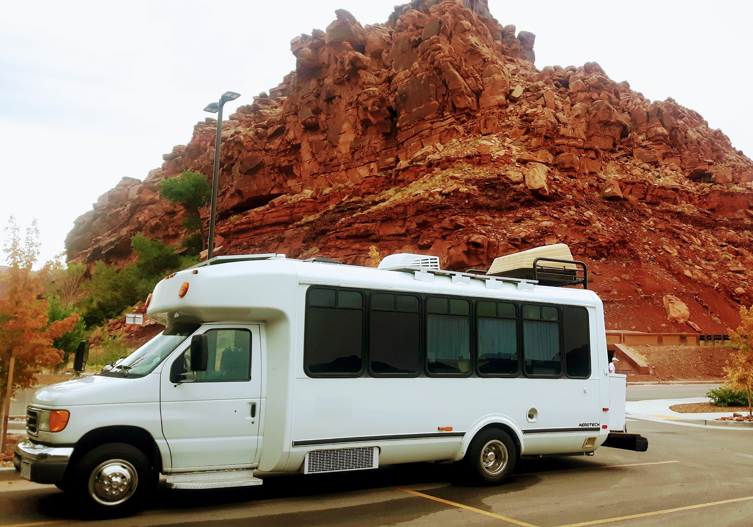 Camperized bus in front of rocks